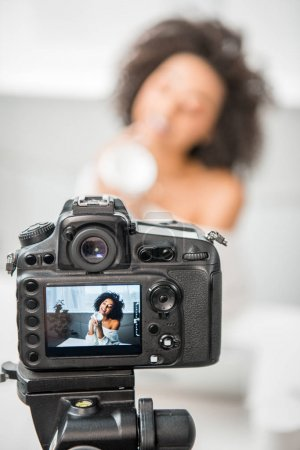 Photo for Selective focus of digital camera with curly african american influencer in braces holding container with cosmetic cream on display - Royalty Free Image
