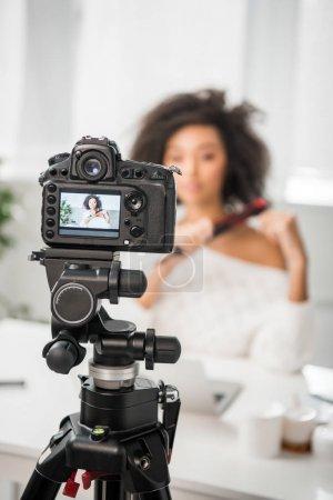 Photo pour Mise au point sélective de l'appareil photo numérique avec influenceur afro-américain bouclé à l'aide d'un lisseur sur l'écran - image libre de droit
