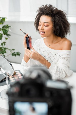 Photo for Selective focus of happy african american video blogger in braces holding palette with lip gloss near digital camera - Royalty Free Image