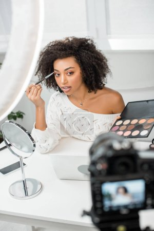 selective focus of beautiful african american video blogger applying eye shadow and looking at digital camera