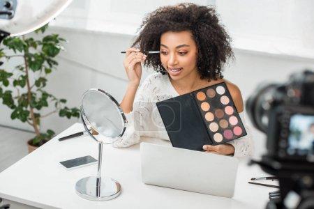 selective focus of cheerful african american video blogger in braces applying eye shadow near digital camera