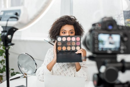 selective focus of curly african american video blogger covering face while holding eye shadow palette near digital camera