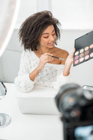 Photo for Selective focus of happy african american video blogger in braces holding cosmetic brush and eye shadow palette near digital camera - Royalty Free Image