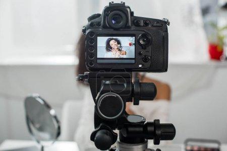 Photo pour Mise au point sélective de l'appareil photo numérique avec heureux blogueur vidéo afro-américain dans les bretelles tenant des gants à lèvres et des pinceaux cosmétiques sur l'affichage - image libre de droit