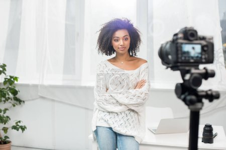 Photo for Selective focus of curly african american influencer standing with crossed arms and looking at digital camera - Royalty Free Image