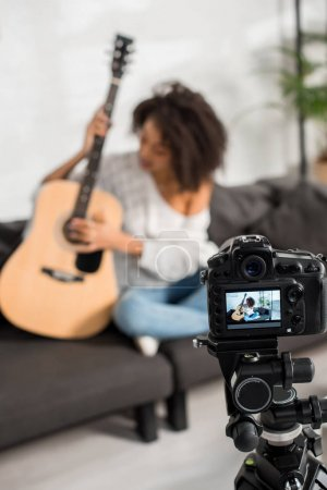 Photo for Selective focus of digital camera with young african american girl playing acoustic guitar on display - Royalty Free Image