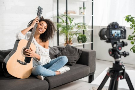 Photo pour Selective focus of happy african american girl in braces holding acoustic guitar and looking at digital camera - image libre de droit