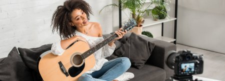Photo for Panoramic shot of cheerful african american girl in braces holding acoustic guitar and looking at digital camera - Royalty Free Image