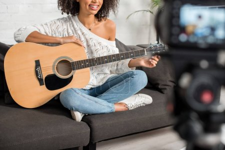 Photo for Cropped view of cheerful african american girl in braces holding acoustic guitar near digital camera - Royalty Free Image
