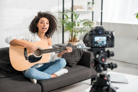 Photo pour Selective focus of young african american girl in braces playing acoustic guitar and singing near digital camera - image libre de droit