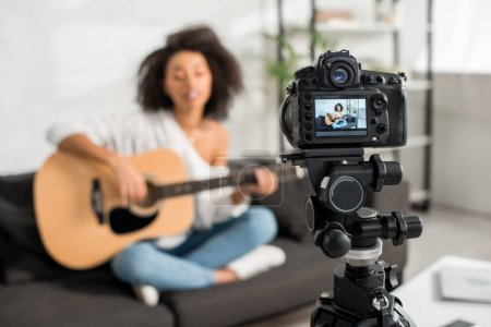 Photo for Selective focus of digital camera with young african american girl in braces playing acoustic guitar and singing on display - Royalty Free Image