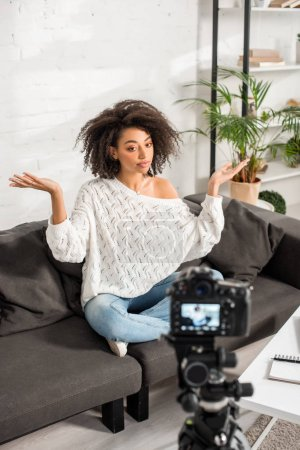 selective focus of young african american influencer sitting on sofa and gesturing near digital camera