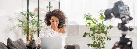 Photo pour Photo panoramique d'un blogueur africain à l'aide d'un ordinateur portable près d'un appareil photo numérique - image libre de droit