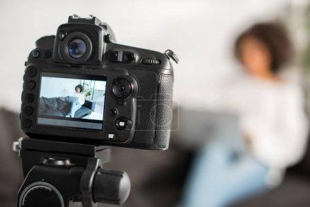 Photo pour Focus sélectif de l'appareil photo numérique avec blogger vidéo african américain utilisant ordinateur portable près de la carte de crédit sur l'affichage - image libre de droit