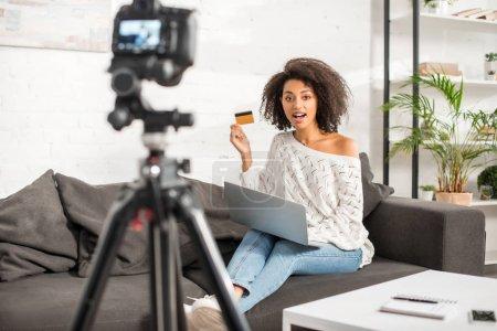 Photo pour Focus sélectif d'un blogueur africain détenteur d'une carte de crédit lors de ses achats en ligne près d'un ordinateur portable et d'un appareil photo numérique - image libre de droit