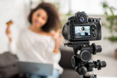 Photo pour Mise au point sélective d'un appareil photo numérique avec une Africaine d'Amérique en attelles tenant la carte de crédit et montrant le pouce sur l'écran - image libre de droit