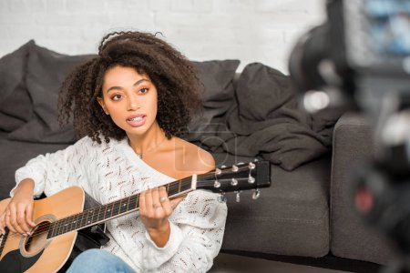 Photo pour Selective focus of young african american girl in braces playing acoustic guitar and looking at digital camera in living room - image libre de droit
