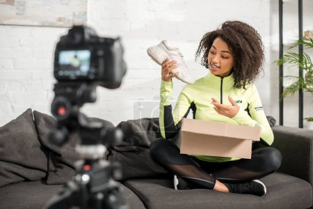 Photo for Selective focus of sportive african american influencer in braces holding new sneaker near box and digital camera - Royalty Free Image