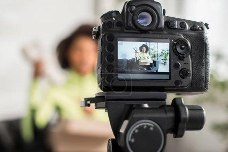 Photo pour Mise au point sélective de l'appareil photo numérique avec influenceur afro-américain sportif tenant une nouvelle sneaker près de la boîte sur l'affichage - image libre de droit