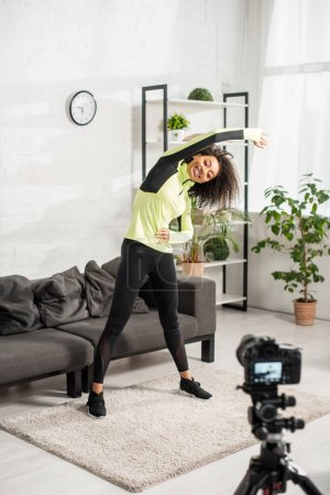 selective focus of sportive african american video blogger in braces exercising near digital camera