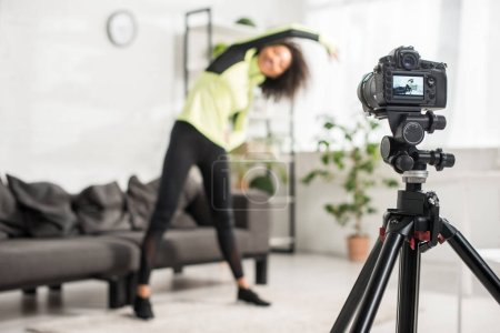 Photo for Selective focus of digital camera with african american video blogger in braces exercising on display - Royalty Free Image
