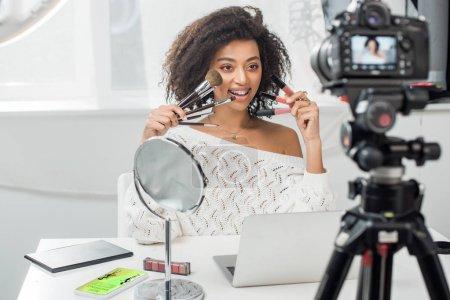Photo pour Foyer sélectif de l'influenceur afro-américain heureux dans les bretelles tenant des gants à lèvres et des pinceaux cosmétiques près du smartphone avec la meilleure application d'achat et appareil photo numérique - image libre de droit