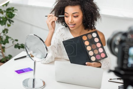 selective focus of cheerful african american video blogger in braces applying eye shadow near smartphone with shopping app and digital camera