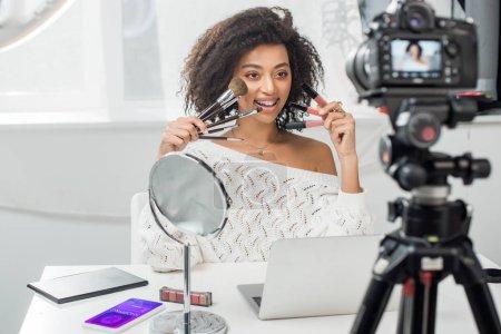 Photo pour Foyer sélectif de l'influenceur afro-américain heureux dans les bretelles tenant des gants à lèvres et des pinceaux cosmétiques près du smartphone avec application shopping et appareil photo numérique - image libre de droit