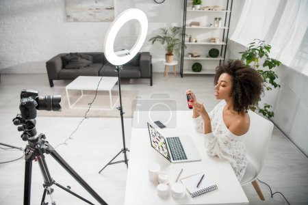 Photo for KYIV, UKRAINE - DECEMBER 10, 2019: african american influencer holding hair straightener near digital camera and laptop with pinterest website - Royalty Free Image