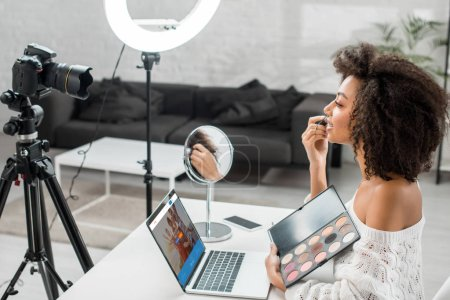 Photo for KYIV, UKRAINE - DECEMBER 10, 2019: side view of african american influencer holding eye shadow palette near laptop with couchsurfing website and digital camera - Royalty Free Image