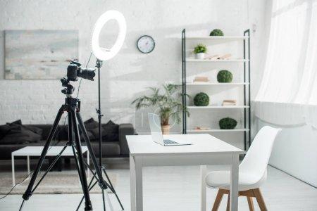 Photo pour Caméra numérique sur trépied près de la lampe à anneau et table avec ordinateur portable - image libre de droit