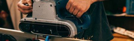 Photo pour Photo panoramique d'un travailleur réparant un ski avec une sableuse à courroie dans un atelier de réparation - image libre de droit