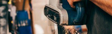 Photo for Panoramic shot of worker repairing ski with belt sander in repair shop - Royalty Free Image
