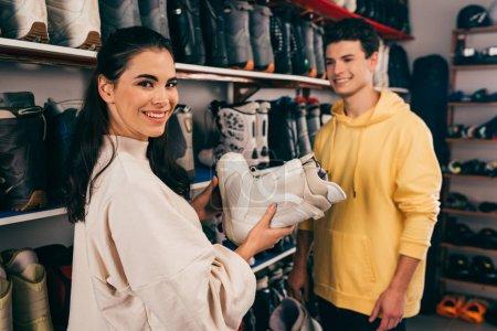 Photo pour Foyer sélectif du client tenant chaussure de ski et travailleur souriant sur le fond dans l'atelier de réparation - image libre de droit