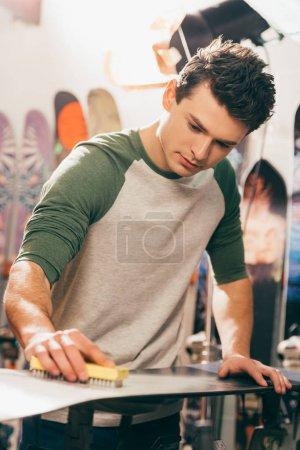 Photo pour Beau travailleur utilisant brosse sur snowboard dans l'atelier de réparation - image libre de droit