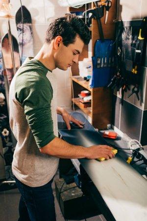 Photo pour Vue latérale du travailleur utilisant une brosse sur snowboard dans un atelier de réparation - image libre de droit