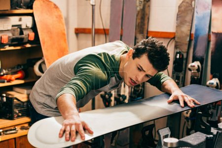 Photo for Handsome worker touching snowboard in repair shop - Royalty Free Image