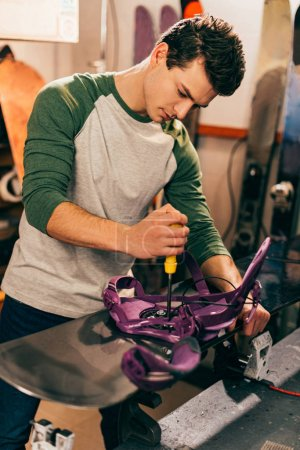 Photo for Worker screwing snowboard binding to snowboard in repair shop - Royalty Free Image
