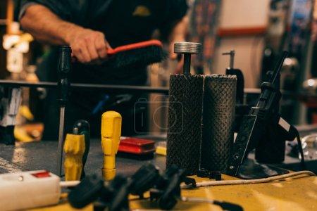 Photo for Selective focus of repair tools and worker using brush on ski in repair shop - Royalty Free Image