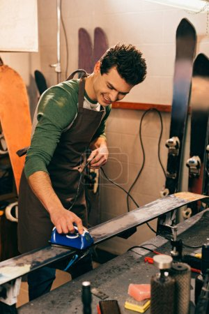 smiling worker waxing ski with wax iron in repair shop
