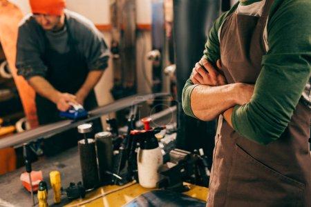 Photo pour Vue en coupe d'un (e) travailleur aux bras croisés et de son collègue utilisant du fer à cire dans un atelier de réparation - image libre de droit