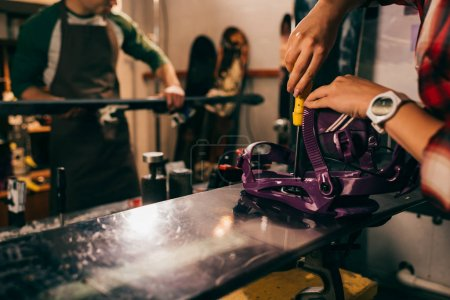 Photo for Cropped view of worker screwing snowboard binding to snowboard in repair shop - Royalty Free Image