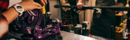 Photo for Panoramic shot of worker screwing snowboard binding to snowboard in repair shop - Royalty Free Image