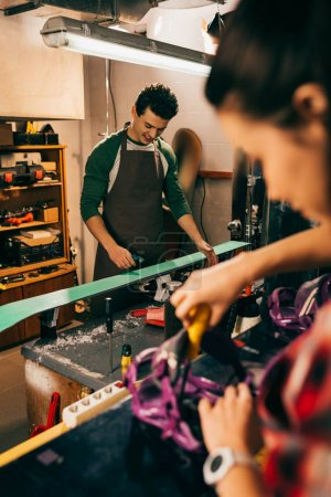 Photo for Selective focus of smiling worker repairing ski and colleague on background - Royalty Free Image