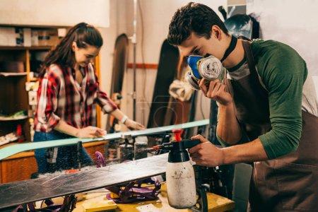 selective focus of worker in respirator spraying on snowboard in repair shop