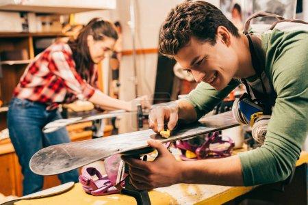 Photo pour Focalisation sélective d'un travailleur souriant utilisant un coupe-boîte sur le ski dans un atelier de réparation - image libre de droit
