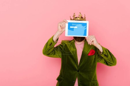 Photo for KYIV, UKRAINE - DECEMBER 3, 2019: man with crown holding digital tablet with twitter app isolated on pink - Royalty Free Image