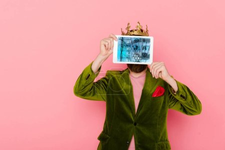 Photo for Man with crown holding digital tablet with health app isolated on pink - Royalty Free Image