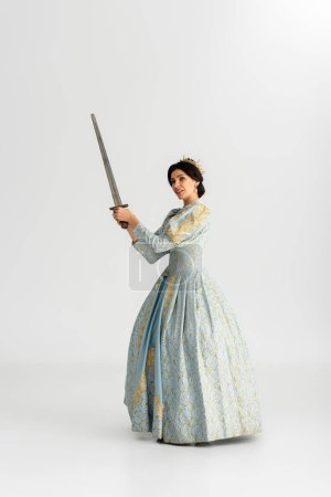Photo pour Attractive queen with crown holding sword on grey background - image libre de droit