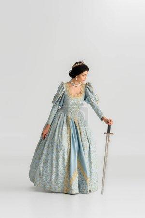 Photo pour Jolie reine avec couronne tenant épée sur fond gris - image libre de droit
